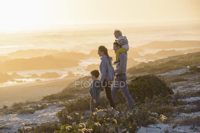 Счастливые молодые семьи, ходить на пляж в яркий закат — стоковое фото