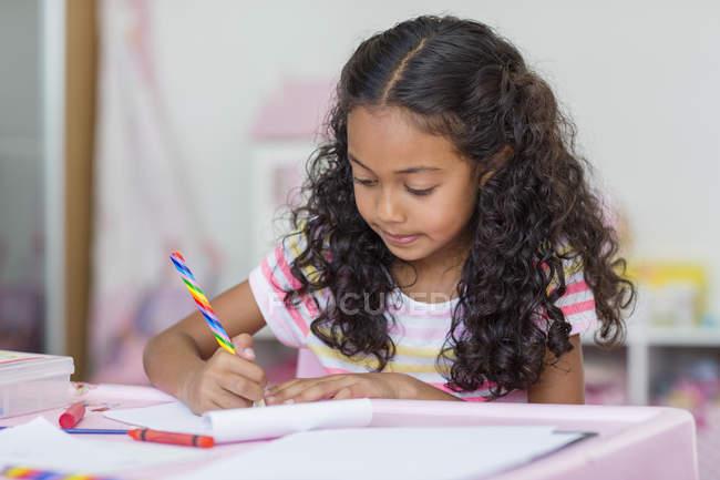 Focused little girl doing homework at table — Stock Photo