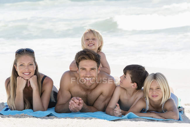 Portrait of happy family lying on blanket on beach — Stock Photo