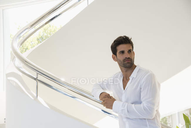Thoughtful man standing on staircase in modern house — Stock Photo