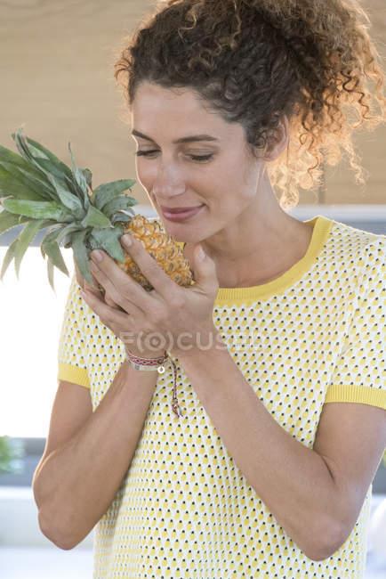 Primo piano della donna che odora di ananas fresco — Foto stock