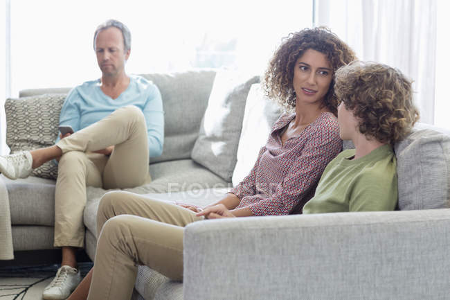 Mother talking to son on sofa while father sitting on background in living room at home — Stock Photo