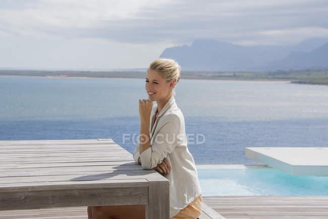 Усміхаючись елегантний молода жінка, сидячи за столом, на березі озера — стокове фото