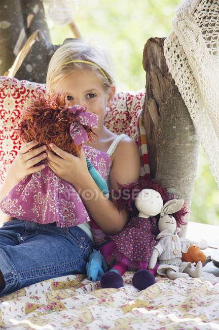 Besinnliches kleines Mädchen hält Spielzeug in Baumhaus — Stockfoto