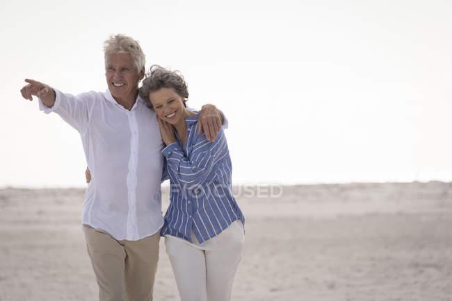 Happy embracing senior couple walking on beach — Stock Photo