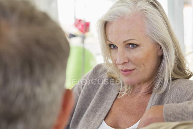 Primer plano de la mujer mayor reflexiva sentada con el marido en el sofá en casa - foto de stock