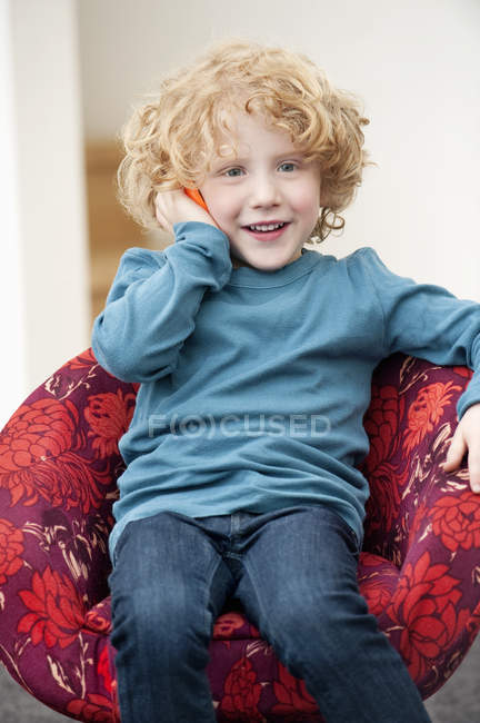 Boy talking on a mobile phone in armchair at home — Stock Photo