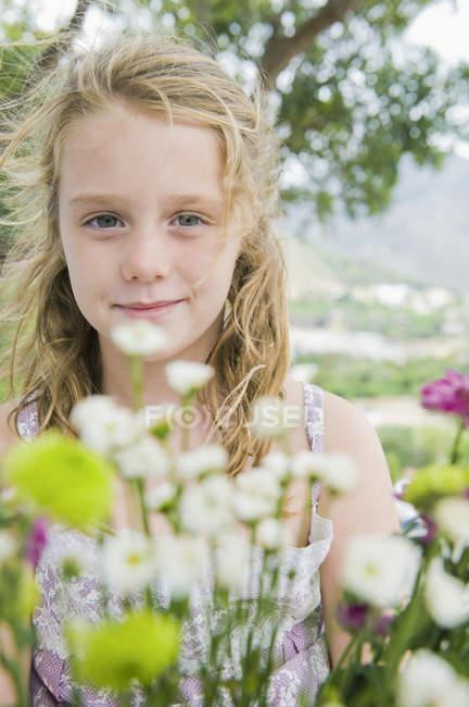 Портрет маленькая блондинка девочка держит цветы — стоковое фото