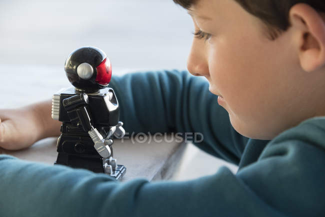 Close-up of boy playing with toy robot — Stock Photo