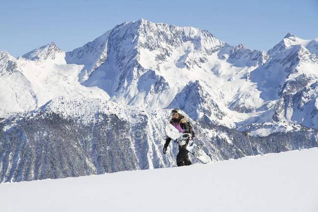 Девочка-подросток, несущая сноуборд в скалистых горах — стоковое фото