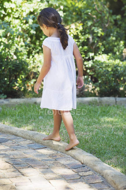 Rear view of little girl in white summer dress walking in sunny garden — Stock Photo