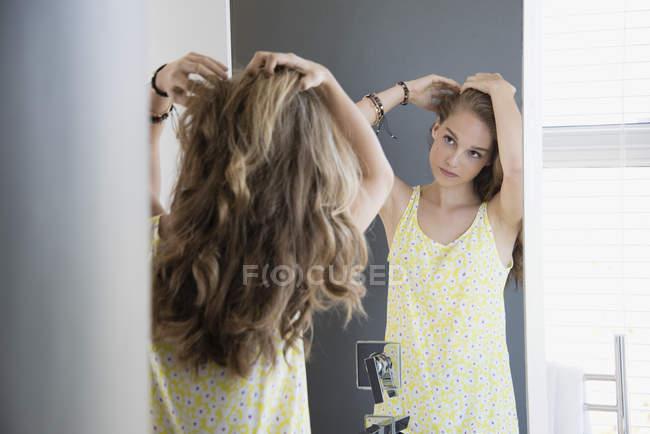 Teenage girl examining hair in mirror — Stock Photo