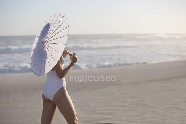Woman in swimsuit with parasol walking on sandy beach — Stock Photo