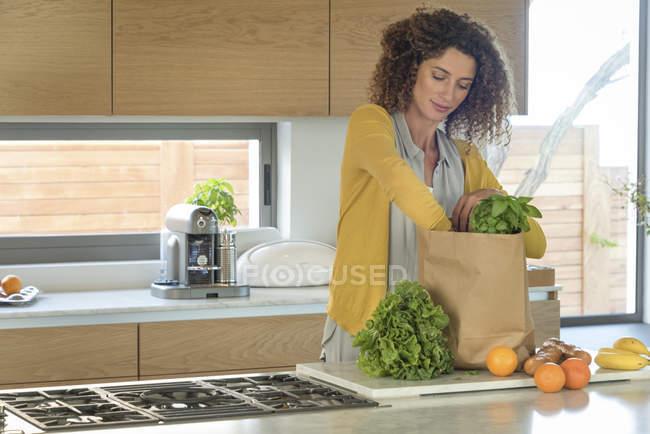 Frau, die Entnahme von Lebensmitteln aus Papiertüte in Küche — Stockfoto