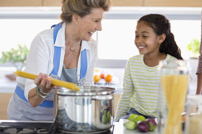 Щаслива старша жінка з внучкою готує їжу на кухні — стокове фото