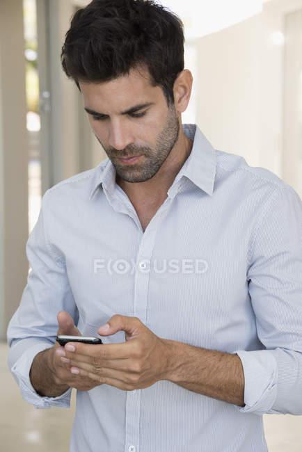 Pensive man in white shirt using smartphone — Stock Photo