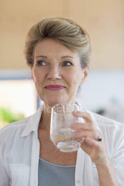 Happy senior woman holding glass of water — Stock Photo