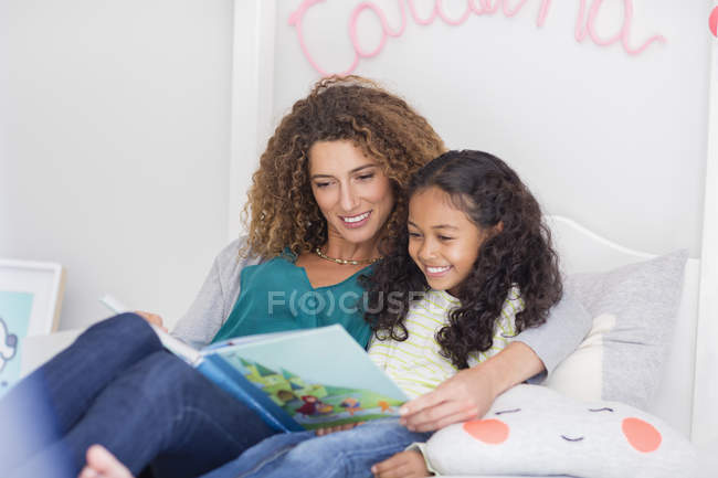 Mother and daughter reading book in bed at home — Stock Photo
