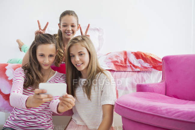 Teenage girls taking selfie with mobile phone at slumber party — Stock Photo