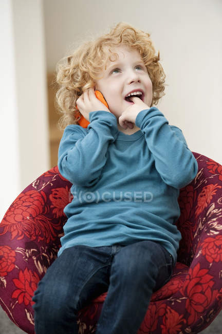 Boy talking on mobile phone with finger in mouth in armchair — Stock Photo