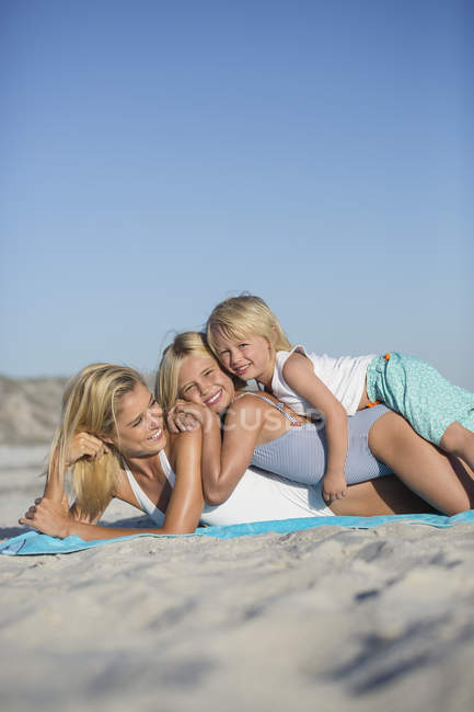 Young woman enjoying on sandy beach with children — Stock Photo