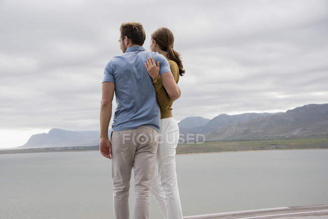 Jeune couple embrassant debout au bord du lac — Photo de stock