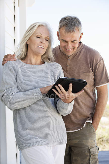 Smiling mature couple using a digital tablet outdoors — Stock Photo