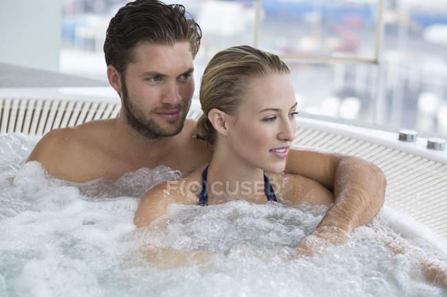 Portrait de couple rire détendu reposant dans un bain à remous — Photo de stock
