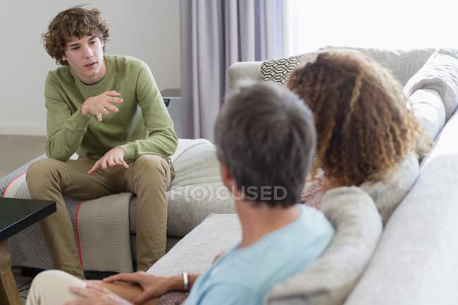 Boy hablar con los padres mientras está sentado en el sofá en la sala de estar en casa - foto de stock
