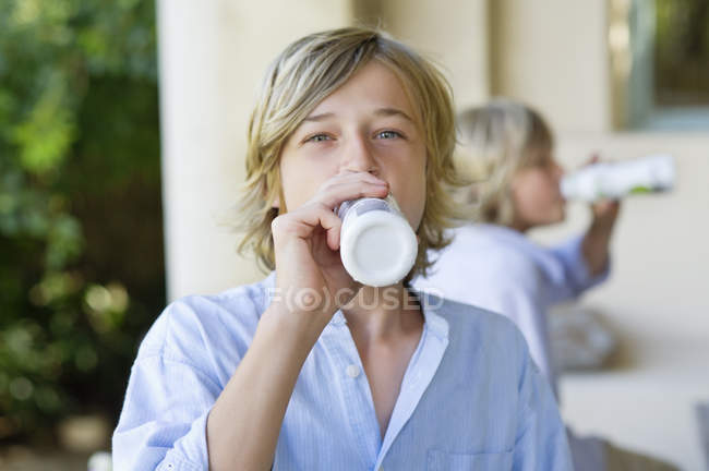 Portrait of teenage boy drinking milk with brother on background — Foto stock