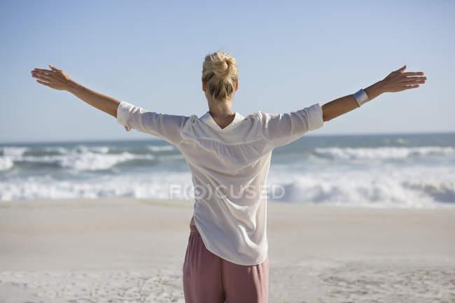 Розслабленої жінка з руки розкритими стояв на сонячному пляжі — стокове фото