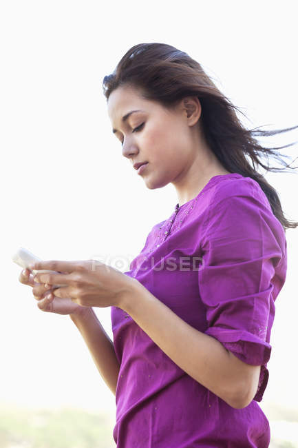 Giovane donna che legge il messaggio di testo sul cellulare — Foto stock