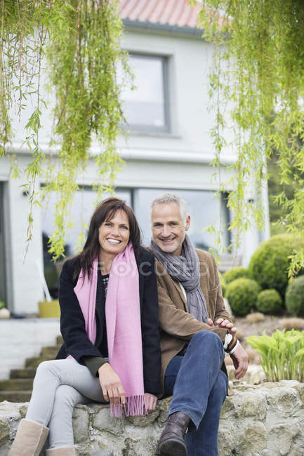Sonriente pareja romántica en jardín en campo - foto de stock