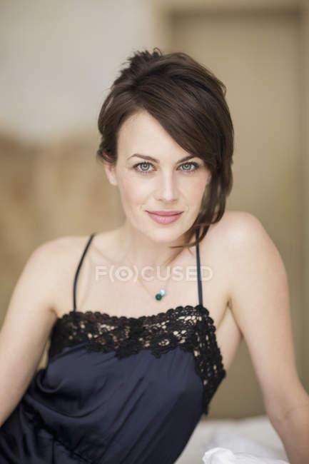 Portrait d'une femme élégante en robe de nuit assis sur le lit — Photo de stock