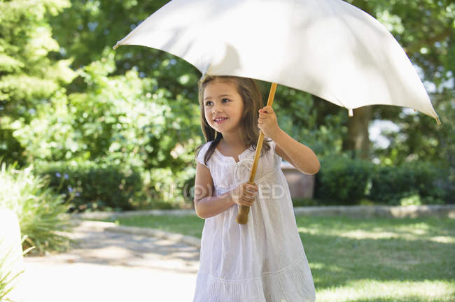 Cute little girl in white summer dress holding umbrella in sunny garden — Stock Photo