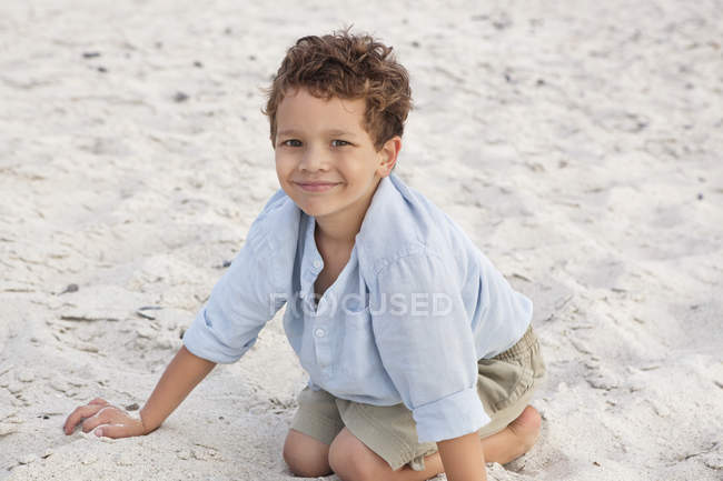 Portrait of smiling little boy playing in sand on beach — Stock Photo