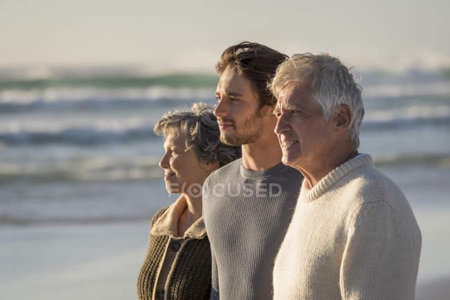 Familia feliz pensativa de pie en la playa juntos y mirando a ver - foto de stock