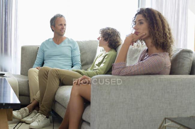 Mujer aburrida sentada en sofá en sala de estar con marido e hijo en el fondo - foto de stock