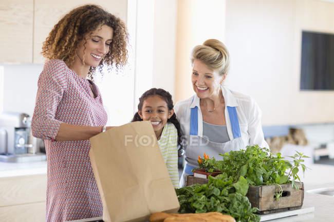 Donna anziana con figlia e nipote che guarda i verdi in cucina — Foto stock