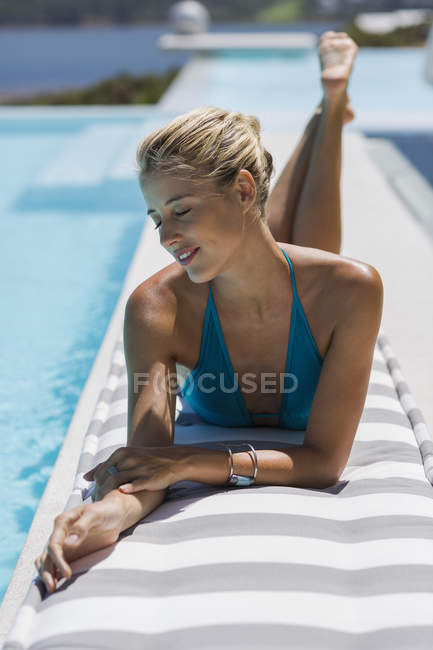 Happy young woman relaxing at poolside — Stock Photo