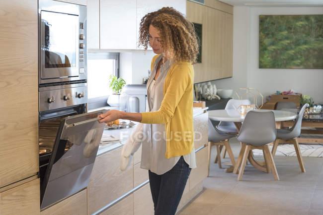 Frau öffnende Tür des Ofens in modernen Küche — Stockfoto