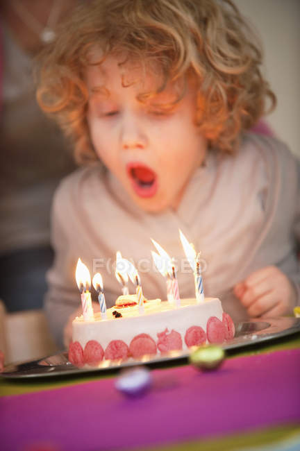 Boy blowing out candles on birthday cake — Stock Photo