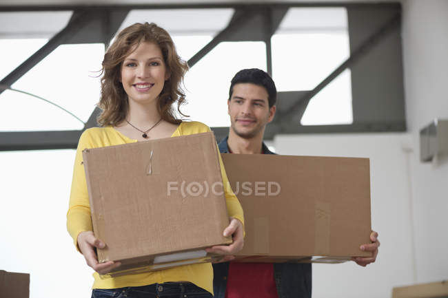 Couple carrying cardboard boxes and smiling — Stock Photo