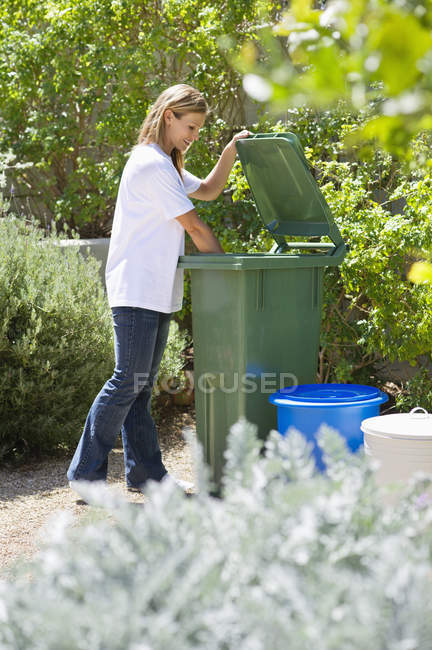 Woman looking into recycling bin outdoors — Photo de stock