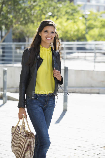 Portrait of smiling woman walking with handbag in city — Stock Photo