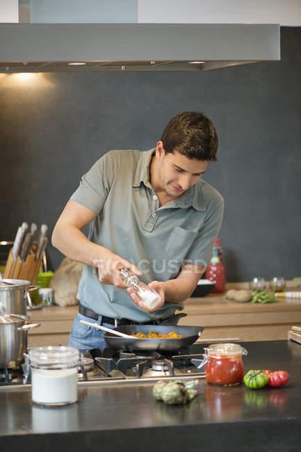 Homme de préparer un repas dans la cuisine moderne — Photo de stock