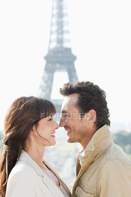 Pareja romántica mirando uno al otro con la Torre Eiffel de fondo, isla de Francia, París, Francia - foto de stock