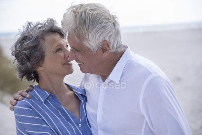 Romantic senior couple standing and kissing on beach — Stock Photo