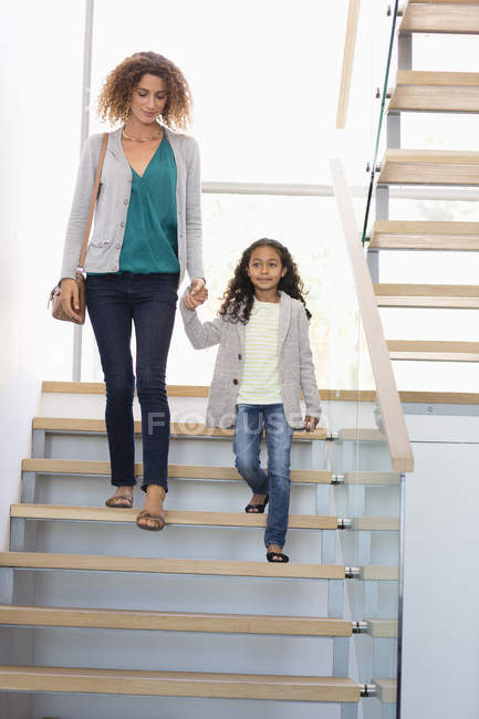 Happy mother and daughter holding hands on staircase in building — Stockfoto