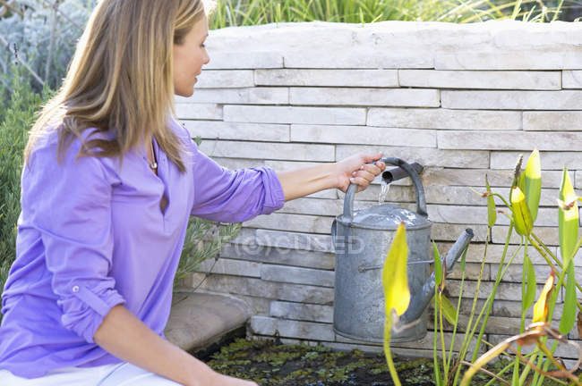 Young woman filling watering can with water — Stock Photo
